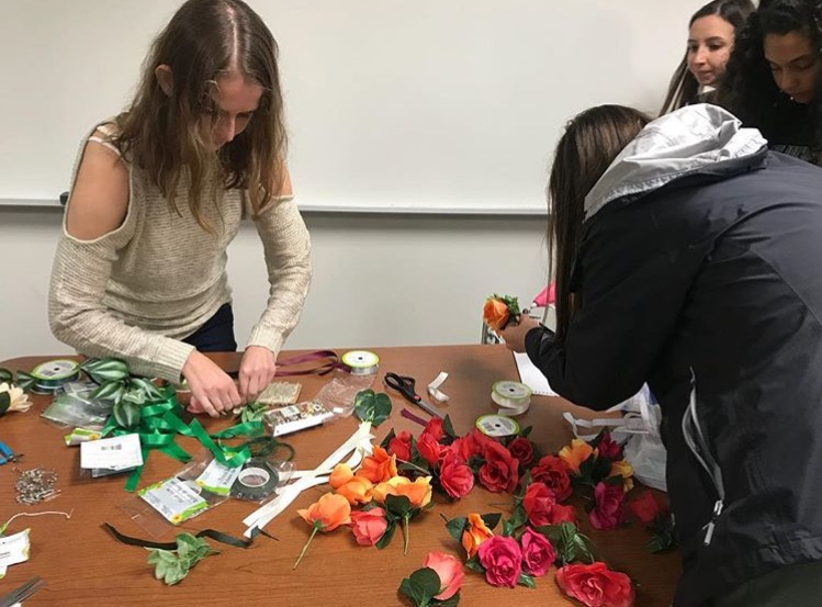 Students surrounding a table with ribbons a bows to create the corsages and Boutonnieres
