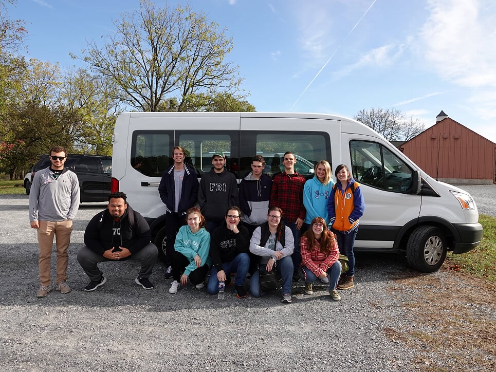 Stevenson history majors pose beside their white, 15 passenger van in which they traveled overnight to Virginia.
