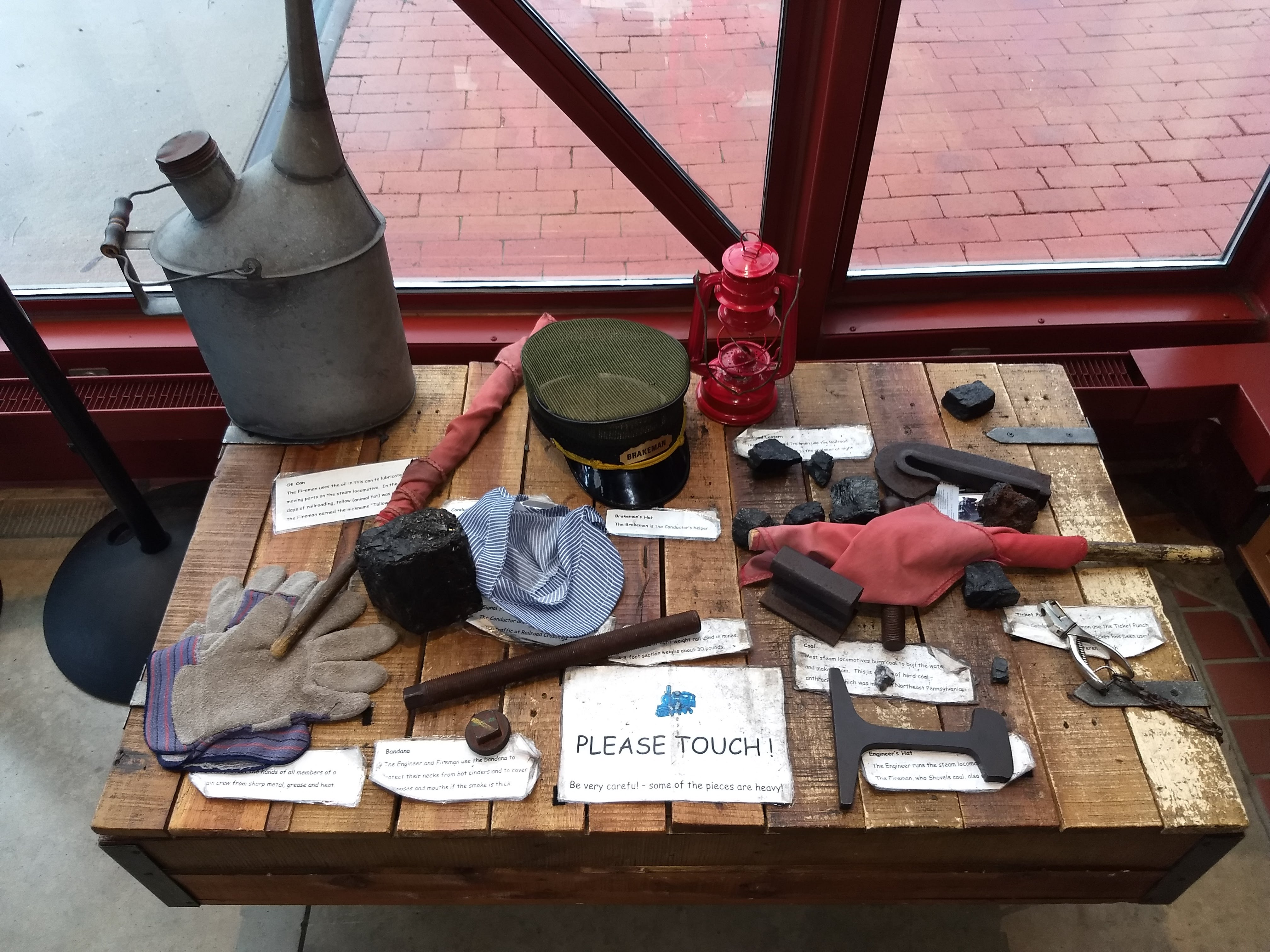 "Picture of table set up with artifacts for people to touch.  A small sign says ""Please Touch."""