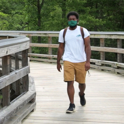 Student walking on campus with mask on