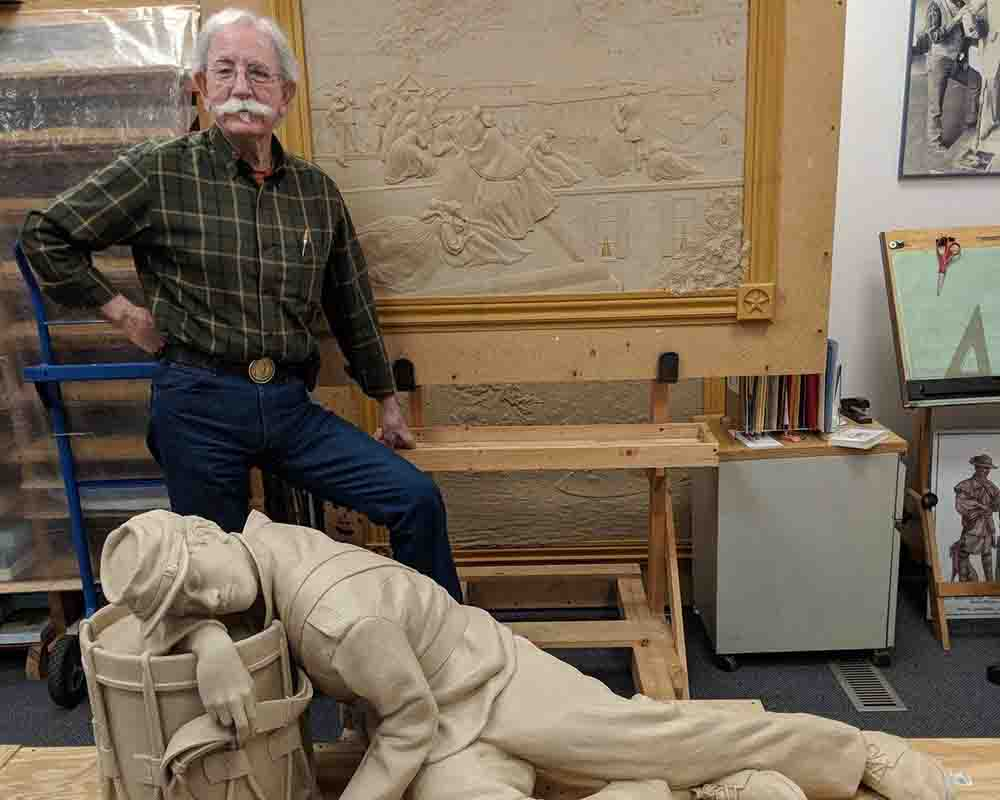 Sculptor Gary Casteel poses with his sculpture of a worn out drummer boy sleeping with his head on his drum.
