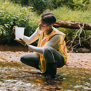 Student taking water samples in a stream