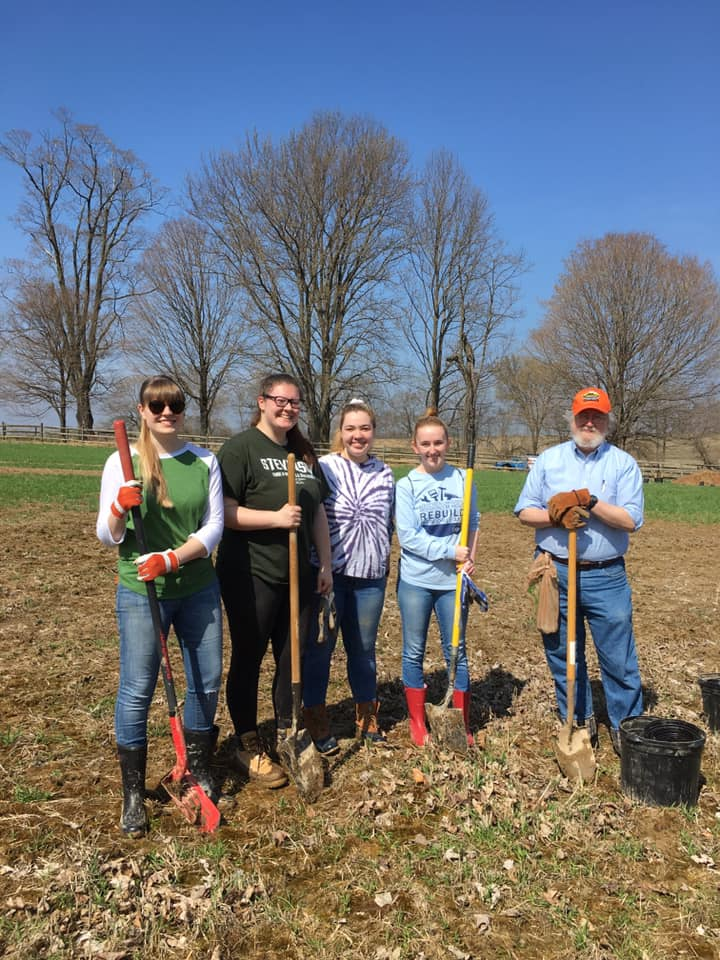 Alex Henry, a group of other PHIST students, and Professopr McGraw standing at Monocacy National Battlefield.  They are leaning on their rakes and shovels.  The day is sunny and bright.