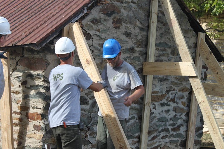 TTAP apprevctices help stabilize a colonial building by using timbers to shore up its walls from the exterior.