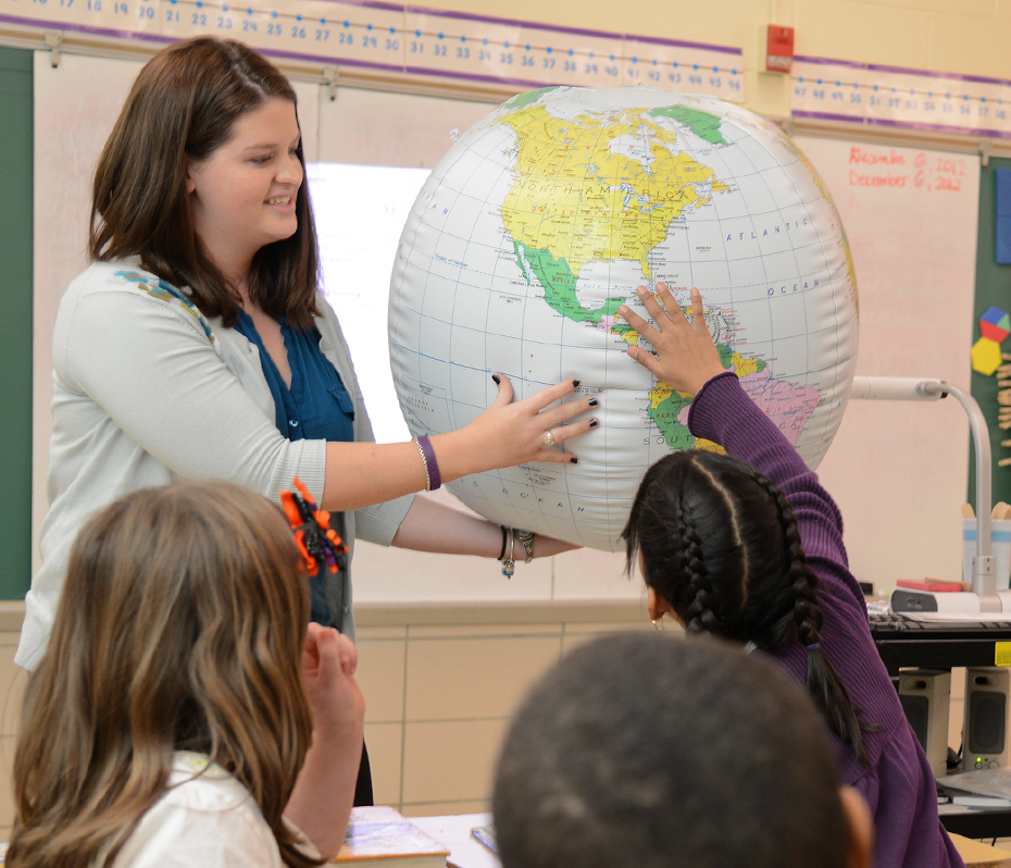 Teacher using a globe with elementary education students