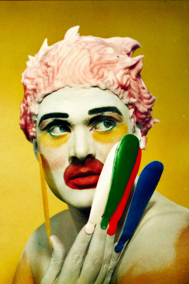 Photograph of Leigh Bowery in costume and makeup against a yellow background.