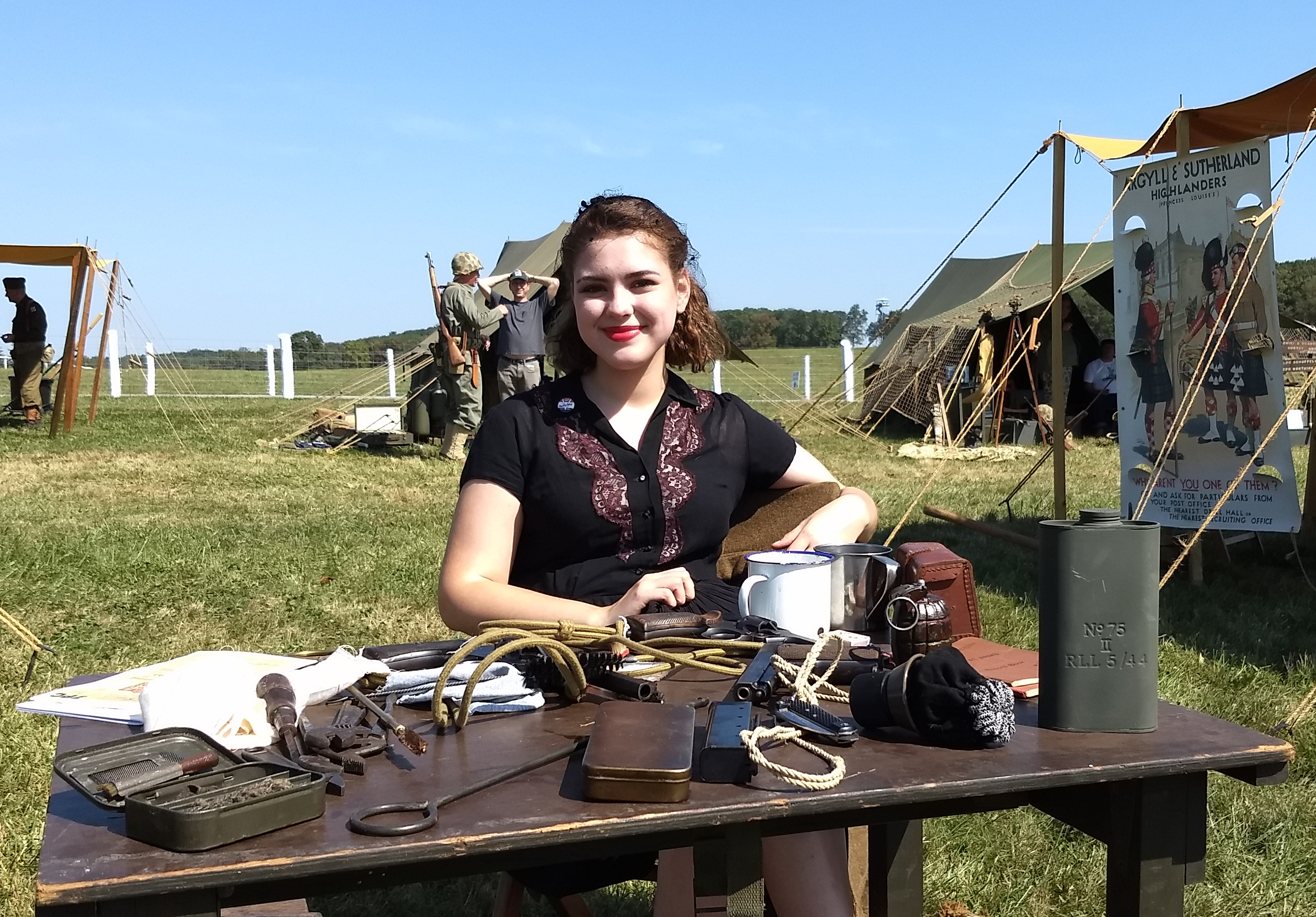 Young woman dressed in a blue dress from the 1940s at a table covered with military equipment from the Scottish argyll & Sutherland Regiment.
