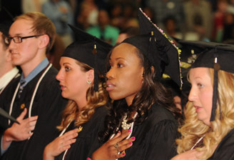 Graduates sitting at ceremony with caps and gowns