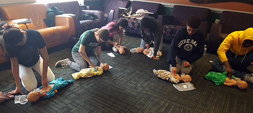 Students work thrir way through infant CPR for their certification.